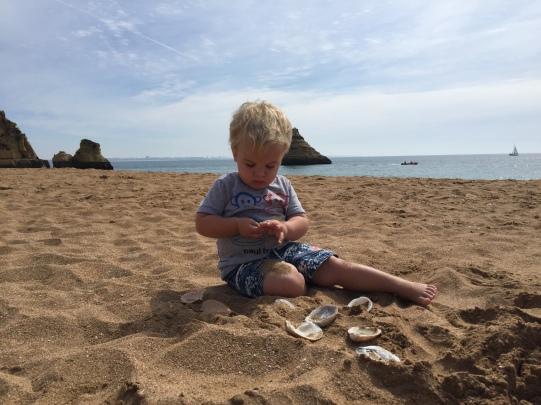 Ro com um ano e 10 meses brincando na areia em Portugal